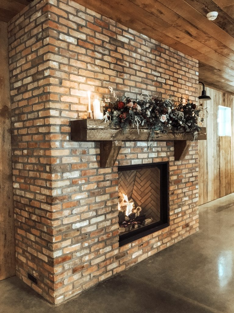 authentic brick fireplace with floral arrangement on wood mantlw with fire from olds alberta