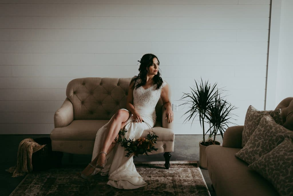 bride sitting on a sette at sweet haven barn in a white room holding a floral hoop