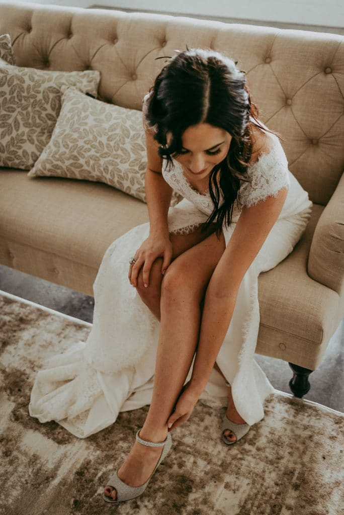 bride sitting on taupe couch adjusting her shoe on her wedding day