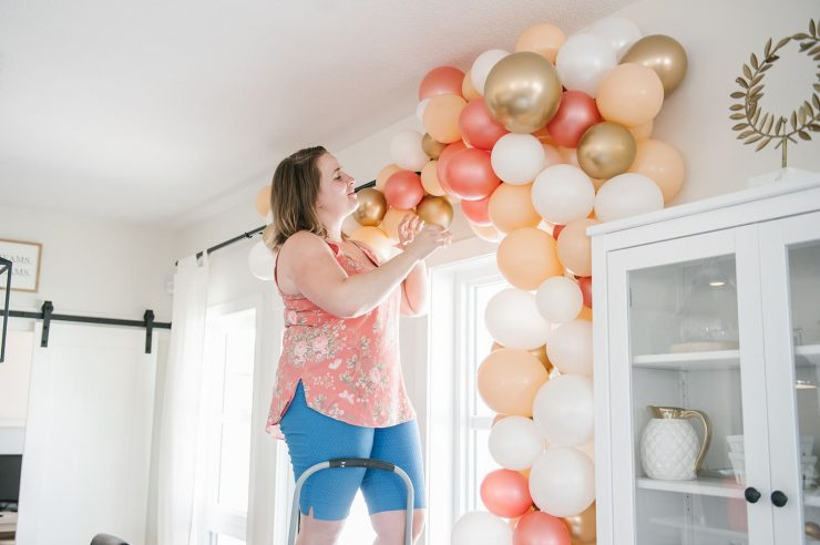 lady building a balloon garland with gold accents while smiling