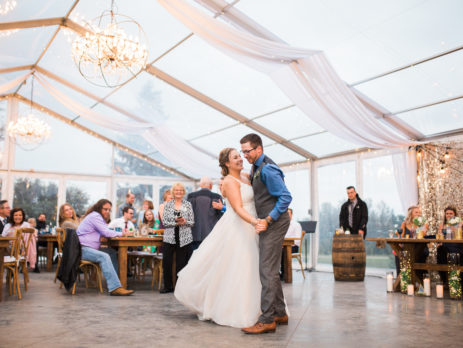bride and groom dancing under clear tent at pine and pond